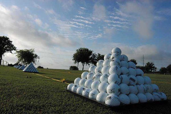 Stacks of golf balls are lined up on the course at The Golf Club at Star Ranch